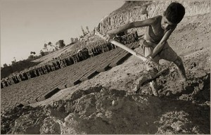 A boy shovels up mud to be converted into bricks in rural Pakistan.