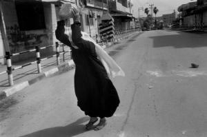 woman break smaller stones for Palestinian youth.Gaza City1993